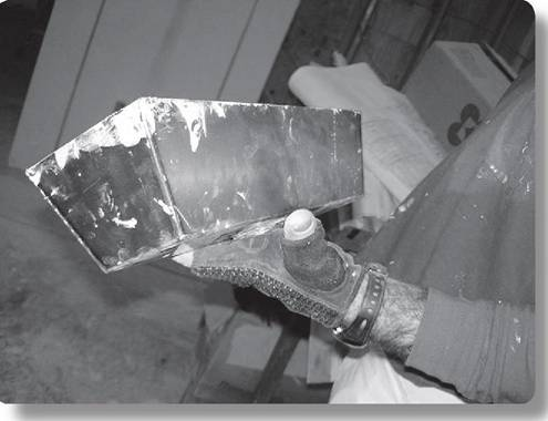 Mud pan held by worker with glove