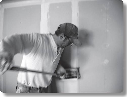 worker using a pneumatic drywall finishing system