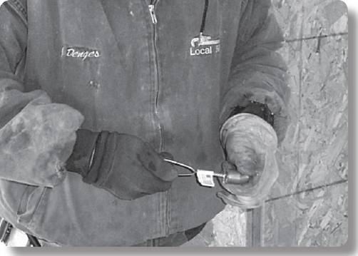 worker holding a wire cleaning tool