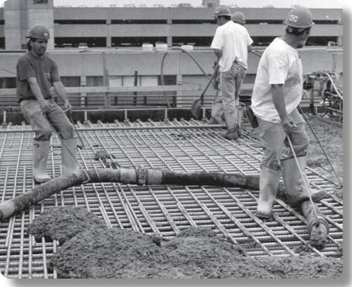workers manually moving concrete filled hoses
